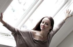 Junge Frau an einem Fenster lizenzfreie stockfotografie