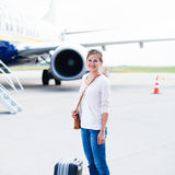 Junge Frau an einem Flughafen Lizenzfreie Stockbilder