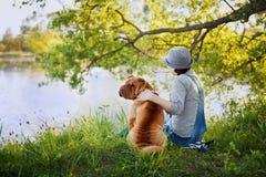 Junge Frau in einem Hut mit Hund Shar Pei, der auf dem Gebiet sitzt und zum Fluss im goldenen Sonnenunterganglicht schaut Lizenzfreie Stockbilder
