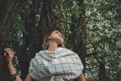 Junge Frau in einem karierten dressstay nahe einem bl?henden Baum stockfotografie