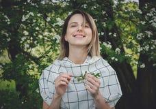 Junge Frau in einem karierten dressstay nahe einem bl?henden Baum stockfoto