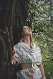 Junge Frau in einem karierten dressstay nahe einem bl?henden Baum lizenzfreie stockbilder
