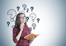 Junge Frau in einem Kleid mit einem Buch, Fragen Lizenzfreies Stockbild