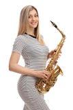 Junge Frau in einem Kleid mit einem Saxophon Stockfoto