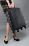 Junge Frau in einem Kleid mit Koffer Stockfoto
