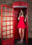 Junge Frau in einem kurzen roten Kleid sprechend am Telefon Lizenzfreie Stockfotos