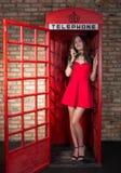 Junge Frau in einem kurzen roten Kleid sprechend am Telefon Stockbild
