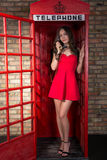Junge Frau in einem kurzen roten Kleid sprechend am Telefon Lizenzfreies Stockbild