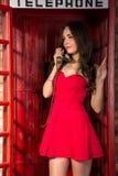 Junge Frau in einem kurzen roten Kleid sprechend am Telefon Stockfoto