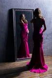 Junge Frau in einem langen rosa Kleid, das nahe bei einem Spiegel steht lizenzfreie stockbilder