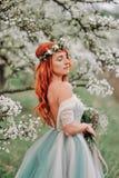 Junge Frau in einem luxuriösen Kleid steht in einem blühenden Garten stockfotografie