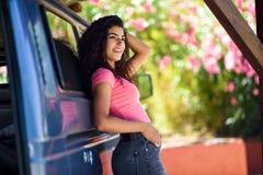 Junge Frau in einem Reisemobil in einem schönen Kampieren mit rosa Blumen lizenzfreies stockfoto