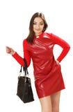Junge Frau in einem roten Kleid mit einer Handtasche Stockfotos