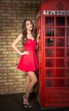 Junge Frau in einem roten Kleid nahe der alten Telefonzelle Lizenzfreie Stockfotografie
