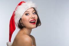 Junge Frau in einem roten Rock und in einem Weihnachtsmann-Hut auf einem hellen backgr Stockbild