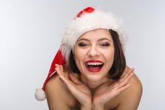 Junge Frau in einem roten Rock und in einem Weihnachtsmann-Hut auf einem hellen backgr Lizenzfreie Stockfotografie