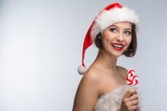Junge Frau in einem roten Rock und in einem Weihnachtsmann-Hut auf einem hellen backgr Stockfotografie