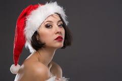 Junge Frau in einem roten Rock und in einem Weihnachtsmann-Hut auf einem hellen backgr Stockfotos