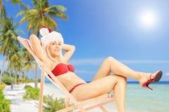 Junge Frau in einem Sankt-Kostüm, das auf einem Sonnenruhesessel auf einem Sein sitzt Stockbilder