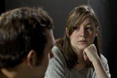 Junge Frau an einem Stützungskonsortium, das auf das Zeugnis des Mannes hört Lizenzfreie Stockfotos
