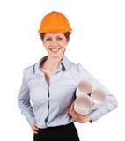 Frau in einem Sturzhelm mit Bauplänen Stockbild