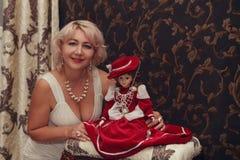 Junge Frau in einem weißen Kleid und eine Puppe in einem Kran kleiden an Stockbild