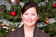 Junge Frau an einem Weihnachtsbaum Stockbild