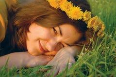 Junge Frau in einem Wreath vom Löwenzahn Lizenzfreie Stockfotos