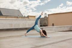 Junge Frau in einer abwärtsgerichteten Haltung des Yoga Hunde, rechtes Bein oben Lizenzfreies Stockbild