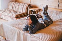 Junge Frau in einer gestrickten Strickjacke, die auf einem Bett sich entspannt Lizenzfreie Stockbilder