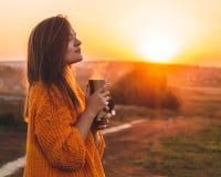 Junge Frau in einer orange Strickjacke mit Porträt der Thermo Schale der Thermosflasche im Freien im weichen sonnigen Tageslicht  stockbilder
