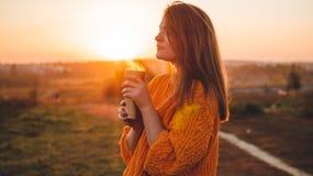 Junge Frau in einer orange Strickjacke mit Porträt der Thermo Schale der Thermosflasche im Freien im weichen sonnigen Tageslicht  lizenzfreies stockbild
