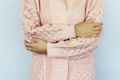 Junge Frau in einer warmen gestrickten Strickjacke faltete Hände auf dem Gurt lizenzfreies stockbild