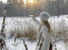 Junge Frau in einer weißen Jacke fotografiert ein Panorama der Küste des Winterwaldsees am Telefon stockfotografie