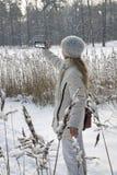 Junge Frau in einer weißen Jacke fotografiert ein Panorama der Küste des Winterwaldsees am Telefon lizenzfreie stockfotografie
