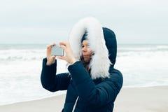 Junge Frau in einer Winterjacke mit einer Haube unter Verwendung eines Handys Lizenzfreies Stockfoto