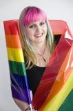 Junge Frau eingewickelt in der Regenbogenmarkierungsfahne Stockfotos