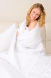 Junge Frau eingewickelt in der weißen Decke stockbilder