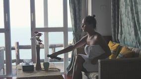 Junge Frau eingewickelt in einem Tuch, das im Bungalow während reisender Getränkkaffee auf Tropeninsel mit Seeansicht fernsieht stock video
