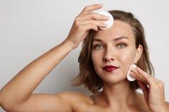 Junge Frau entfernt den weißen Make-upschwamm und betrachtet die Kamera Stockbilder
