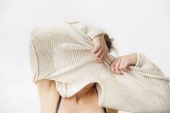 Junge Frau entfernt ihre Strickjacke und bedeckt ihr Gesicht Stockbild
