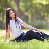 Junge Frau entspannen sich im Park auf grünem Gras stockfotos