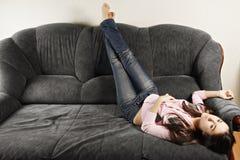 Junge Frau entspannt auf Sofa Stockbild
