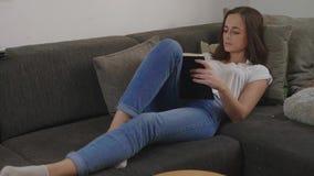 Junge Frau entspannt sich in ihrem Wohnzimmer beim Ablesen eines Buches stock video footage