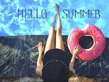 Junge Frau entspannt sich mit Donut im Swimmingpool am Kurort Ansicht von oben stockfotografie