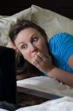 Junge Frau erschrak beim Überwachen des Films lizenzfreie stockfotos
