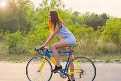 Junge Frau fährt auf ein Fahrrad auf der Straße im Park in der SU Lizenzfreie Stockfotos