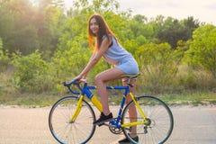 Junge Frau fährt auf ein Fahrrad auf der Straße im Park in der SU Stockbilder