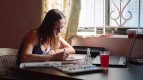Junge Frau führt eine Lektion im Aquarell, das online zu Hause malt stock footage