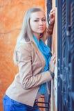 Junge Frau am Fenster mit geschmiedeten Stangen Stockbilder